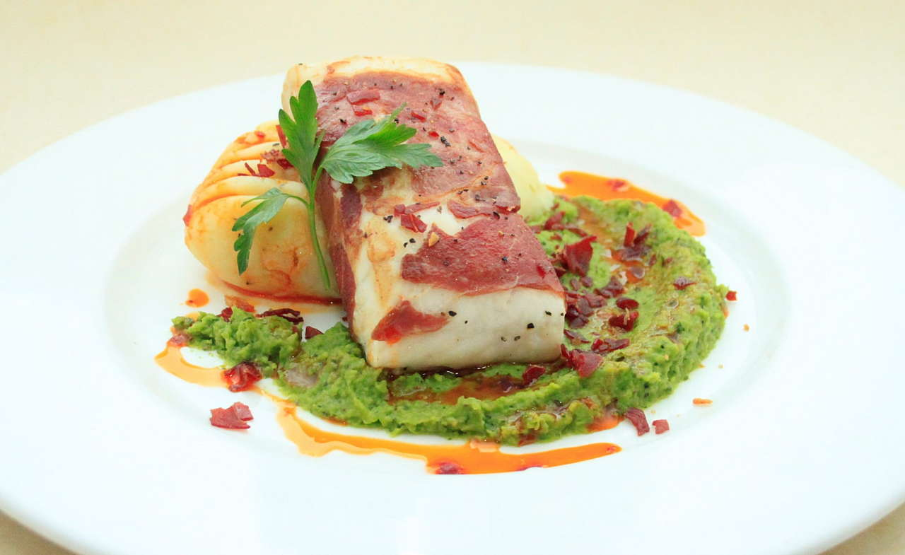Hake with serrano ham mash & peas with red pepper oil